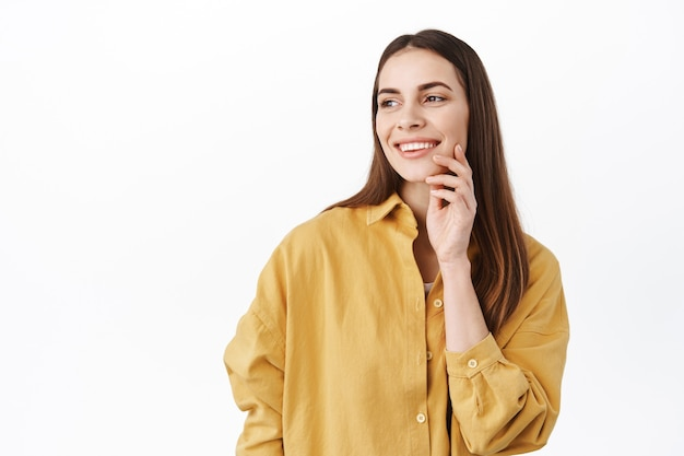 Young smiling woman with long hair and beauty face, touching facial skin and looking dreamy aside, reading promotional text on left side, daydreaming, standing over white wall
