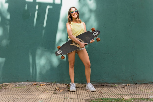 Young smiling woman with longboard against green wall