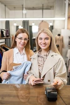プラスチックカードを持った若い笑顔の女性と新しいスウェットシャツを着た母親が新しい服の支払いをしながら支払いカウンターのそばに立っています