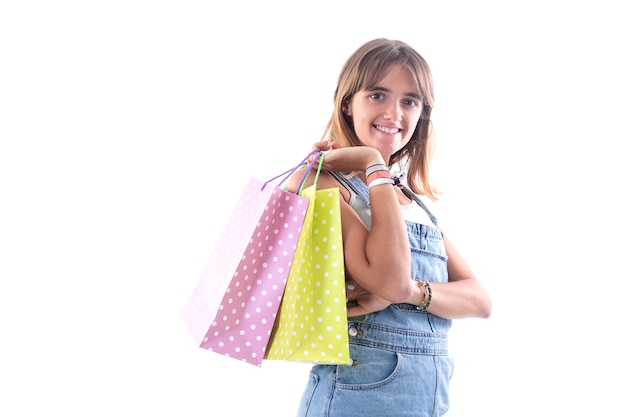 Young smiling woman with shopping bags against white