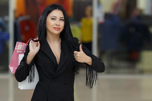 Молодая улыбающаяся женщина с хозяйственными сумками делает большой палец вверх в торговом центре, copyspace