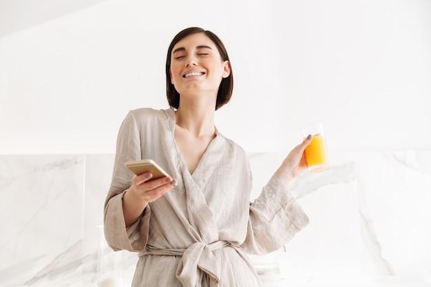 Молодая женщина улыбается с короткими темными волосами, стоя на кухне и пить свежий апельсиновый сок, в то время как в чате на мобильном телефоне