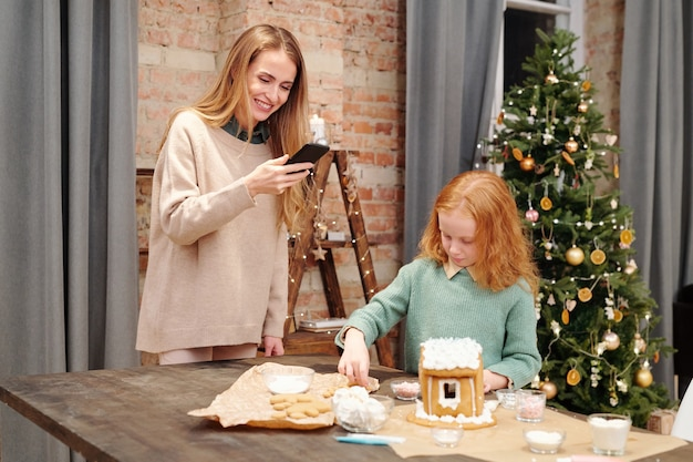 Young smiling woman with smartphone taking photo of homemade gingerbread house while standing by her cute daughter at home