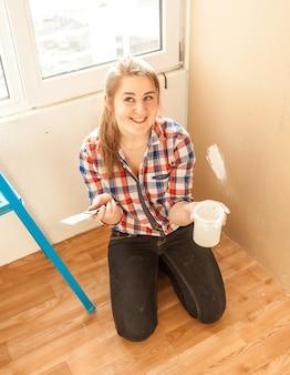Молодая улыбающаяся женщина-работник, держащая шпатель и замазку