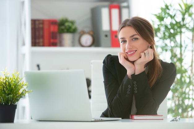 Young smiling woman working at a desk with a laptop in an office