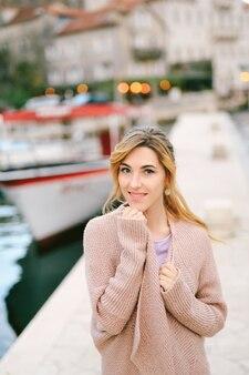 의 배경에 대해 부두에 서 있는 동안 따뜻한 재킷에 싸인 젊은 웃는 여자