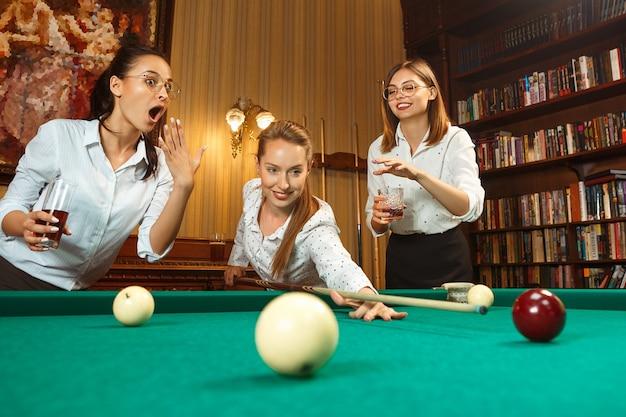 Giovani donne sorridenti che giocano a biliardo in ufficio oa casa dopo il lavoro.