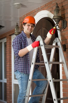 Young smiling worker in hardhat repairing outdoor lamp at house