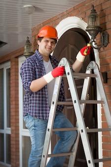 집에서 야외 램프를 수리하는 hardhat에 젊은 웃는 작업자