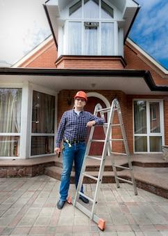 아름 다운 새로 지어진 집에 대 한 포즈 젊은 웃는 작업자