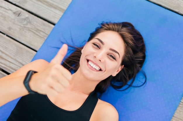 Молодая улыбающаяся спортивная женщина лежит на циновке и показывает палец вверх.
