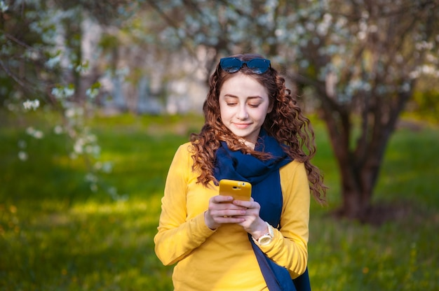 Young smilling woman standing in a blooming garden and writes on mobile phone. blooming cherry