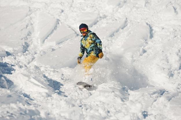 パウダーマウンテンスロープに乗って明るいスポーツウェアの若いスノーボーダー