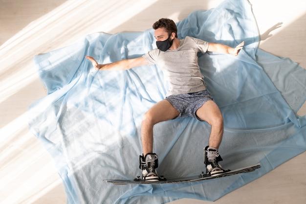 Молодой сноубордист в лицевой маске лежит на полу дома и представляет, что катается на сноуборде в горах после карантина