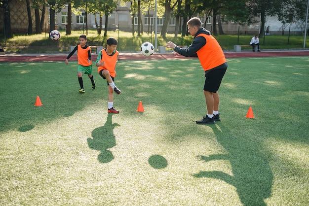 若いサッカーのコーチが10代の選手に指示する