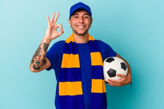 青の背景に分離されたボールを持っている若いサッカーファンの男は、陽気で自信を持って大丈夫なジェスチャーを示しています。