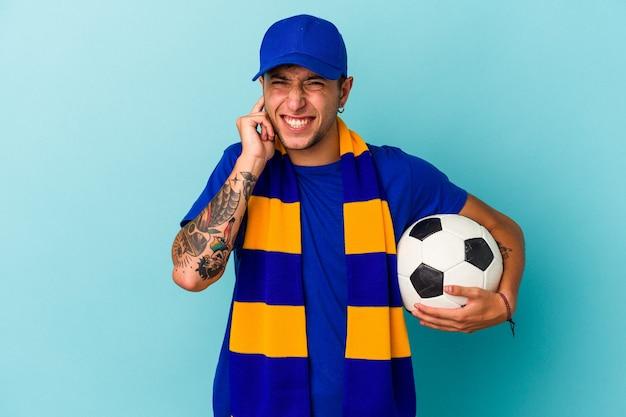手で耳を覆う青い背景に分離されたボールを保持している若いサッカーファンの男。