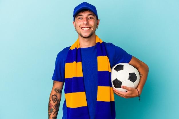 Молодой человек футбольного фаната, держащий мяч на синем фоне, счастливый, улыбающийся и веселый.