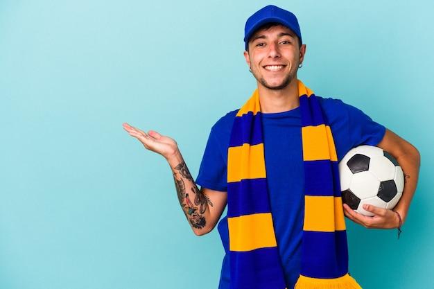 手のひらにコピースペースを示し、腰に別の手を保持している青い背景で隔離のボールを保持している若いサッカーファンの男。
