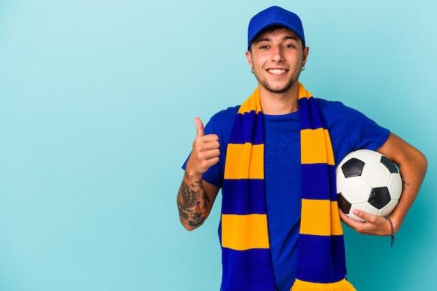 笑顔と親指を上げて青い背景で隔離のボールを保持している若いサッカーファンの男