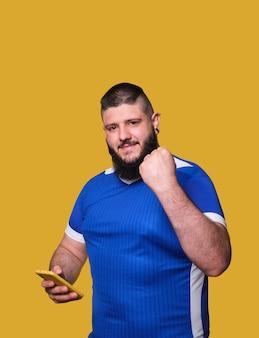 승리의 몸짓으로 문장과 수염을 가진 젊은 축구 팬은 스포츠 베팅에 휴대 전화를 사용합니다.