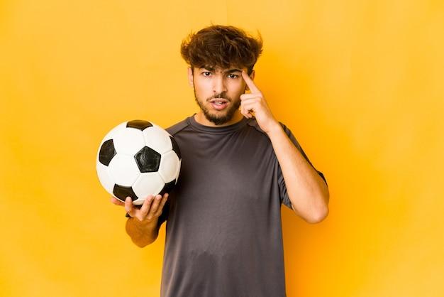 人差し指で失望のジェスチャーを示す若いサッカー選手のインド人。