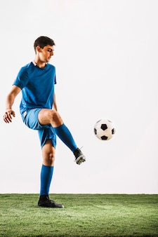 Young soccer player juggling ball