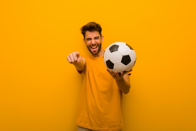 Young soccer player man cheerful and smiling