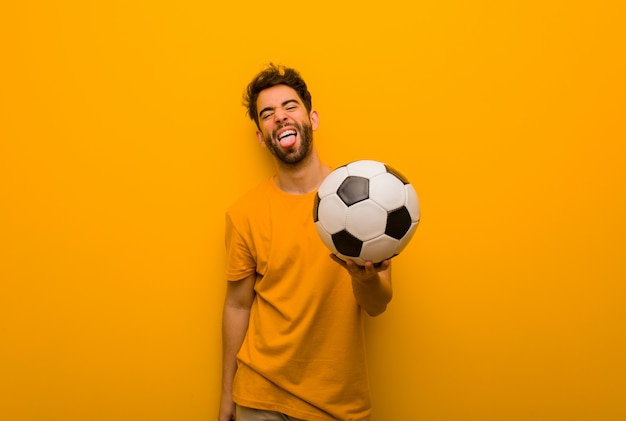 Young soccer player man funnny and friendly showing tongue