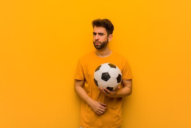 まっすぐ前を見ている若いサッカー選手の男