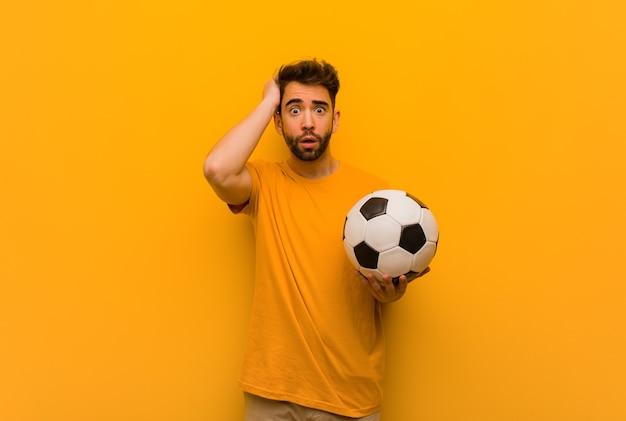心配して圧倒される若いサッカー選手の男
