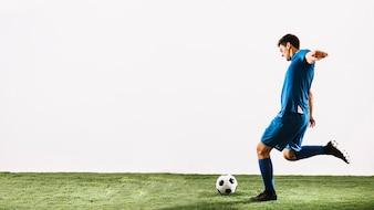 若いサッカー選手ボールを撮影