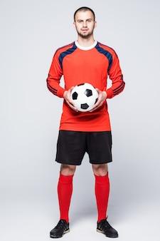 Молодой футболист с мячом, одетый в красную майку перед белым