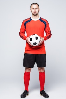 Young soccer player with ball dressed in red jersey in front of white