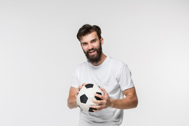 Young soccer player with ball in front of white wall