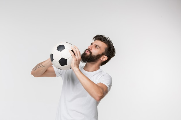 Young soccer player with ball in front of white