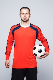 Young soccer player with ball under hand dressed in red jersey in front of white