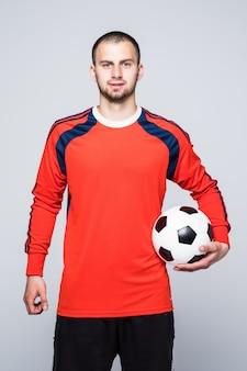 Молодой футболист с мячом под рукой, одетый в красную майку перед белым