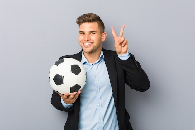 Young soccer trainer showing victory sign and smiling broadly.