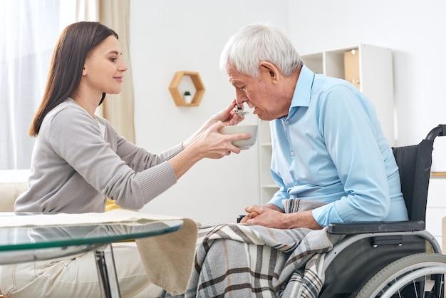 高齢者の口でスープとスプーンでボウルを保持している若いソーシャルワーカーは、彼が食事を手伝っている間車椅子に座っている