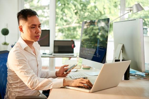 プログラミングコードをチェックするときにラップトップで作業しているスマートフォンを手に若いソフトウェアエンジニア
