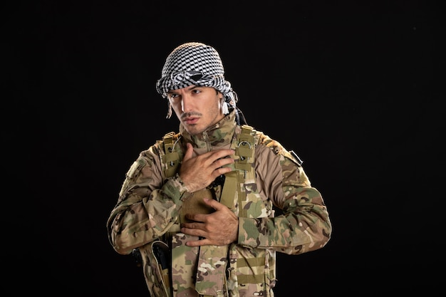 Young soldier in camouflage on a black wall