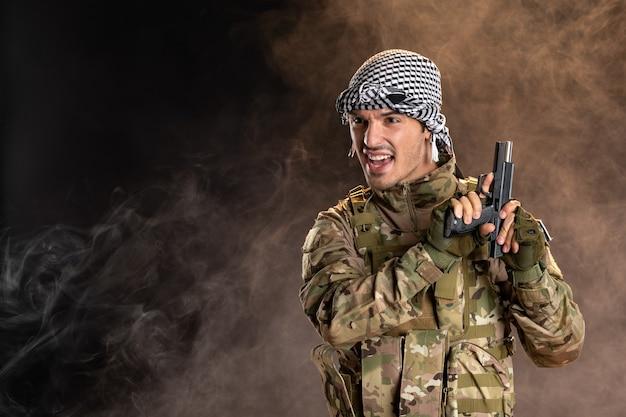Giovane soldato in mimetica che ricarica la pistola sul muro fumoso scuro