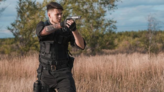 Молодой солдат в черной форме, целится из пистолета