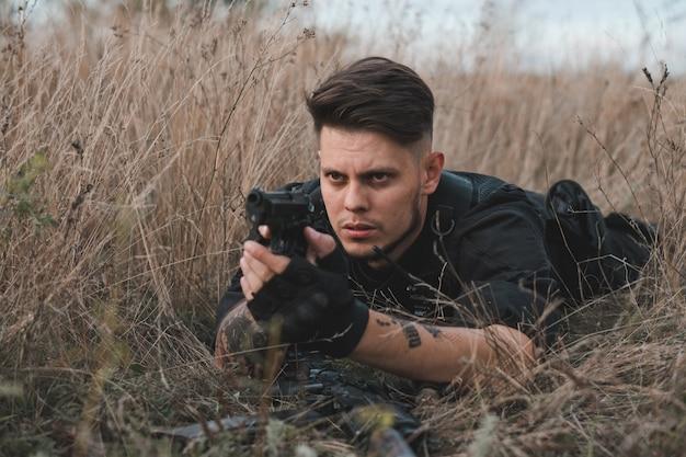 Молодой солдат в черной форме, лежа и целится из пистолета