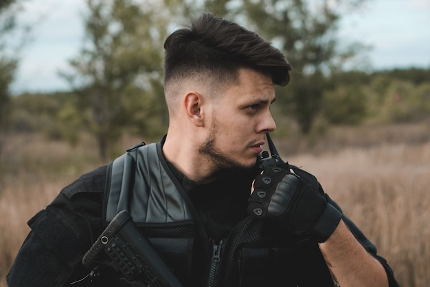 Молодой солдат в черной форме репортаж по радио