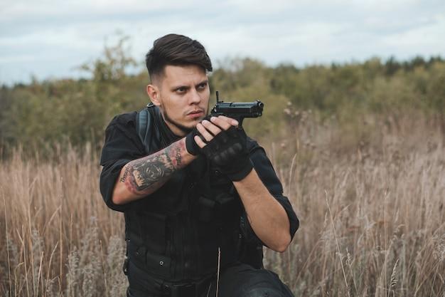 Молодой солдат в черной форме сидит и целится из пистолета