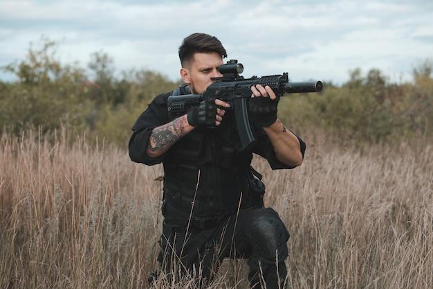 Молодой солдат в черной форме сидит и целится из штурмовой винтовки