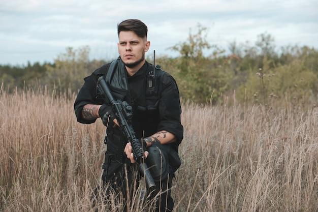 Молодой солдат в черной форме сидит с автоматом