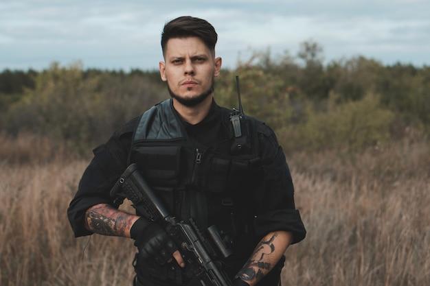アサルトライフルと黒い制服を着た若い兵士